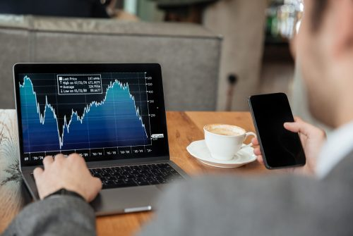 Cropped image of business man sitting by the table in cafe and analyzing indicators on laptop computer while using smartphone